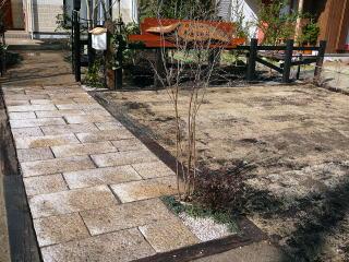 路から門柱までは枕木で囲われた御影石、途中2箇所に植栽が施されています。