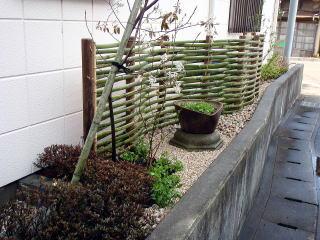エアコンの室外機の前には少し変わった竹垣。 竹垣の前にはフラワーポットを。