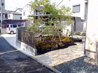 通りからの風景。常緑、落葉から紅葉する樹木を植栽。今回はブルーベリーやジュンベリーなど実物の樹木も植えて四季折々を楽しめるような庭になりました。