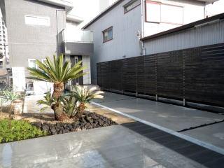 隣家との境には板塀。高さ2mの特大サイズです。車を駐車した場合の通路として真ん中にはテニソンベイパーを使用(黒っぽいところ)。